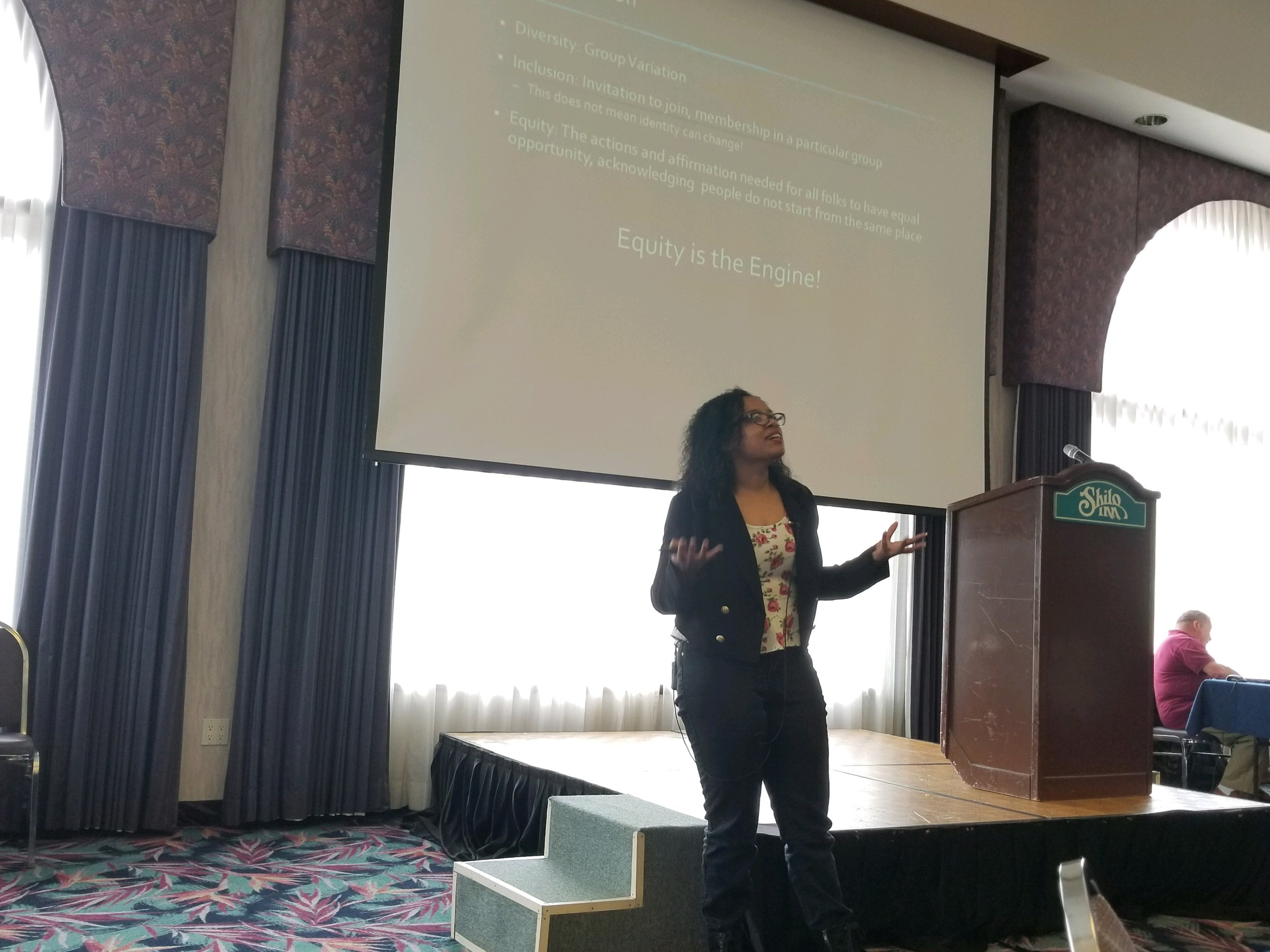 """Photo Description: ChrisTiana ObeySumner standing in front of a large screen, arms outstretched, giving a training. The screen says """"Equity is the Engine."""""""