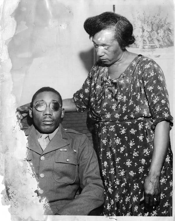 Picture description: Sgt. Issac Woodword sitting in uniform, wearing sunglasses due to blinding. He is accompanied by his mother, who is standing to his left in a dark, floral dress.