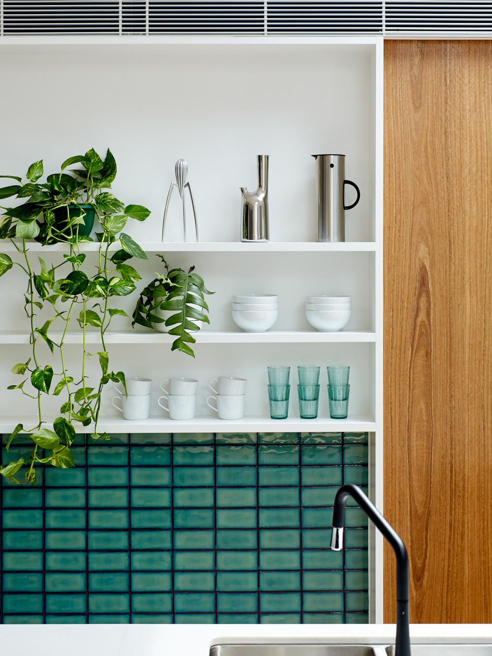 Kitchen with white shelves and a green tile splashback