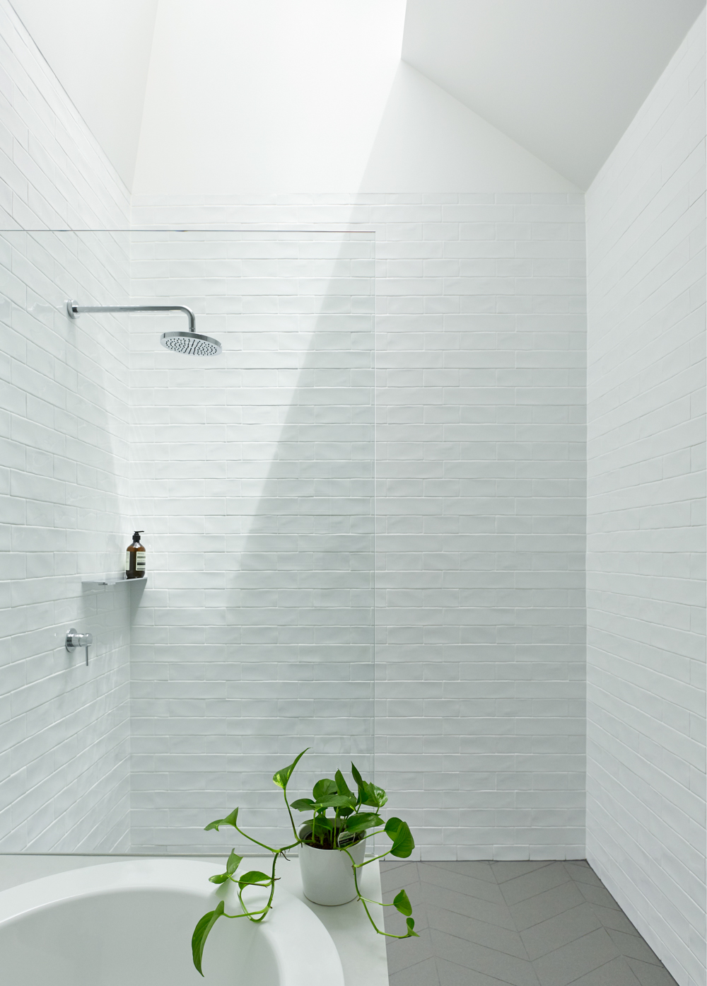 White bathroom with skylight above shower