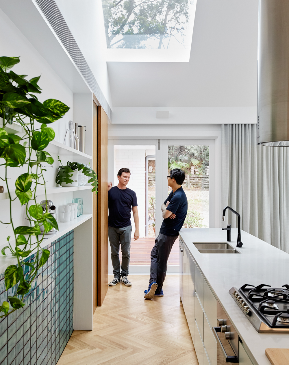 Looking down kitchen with two people talking with skylight above