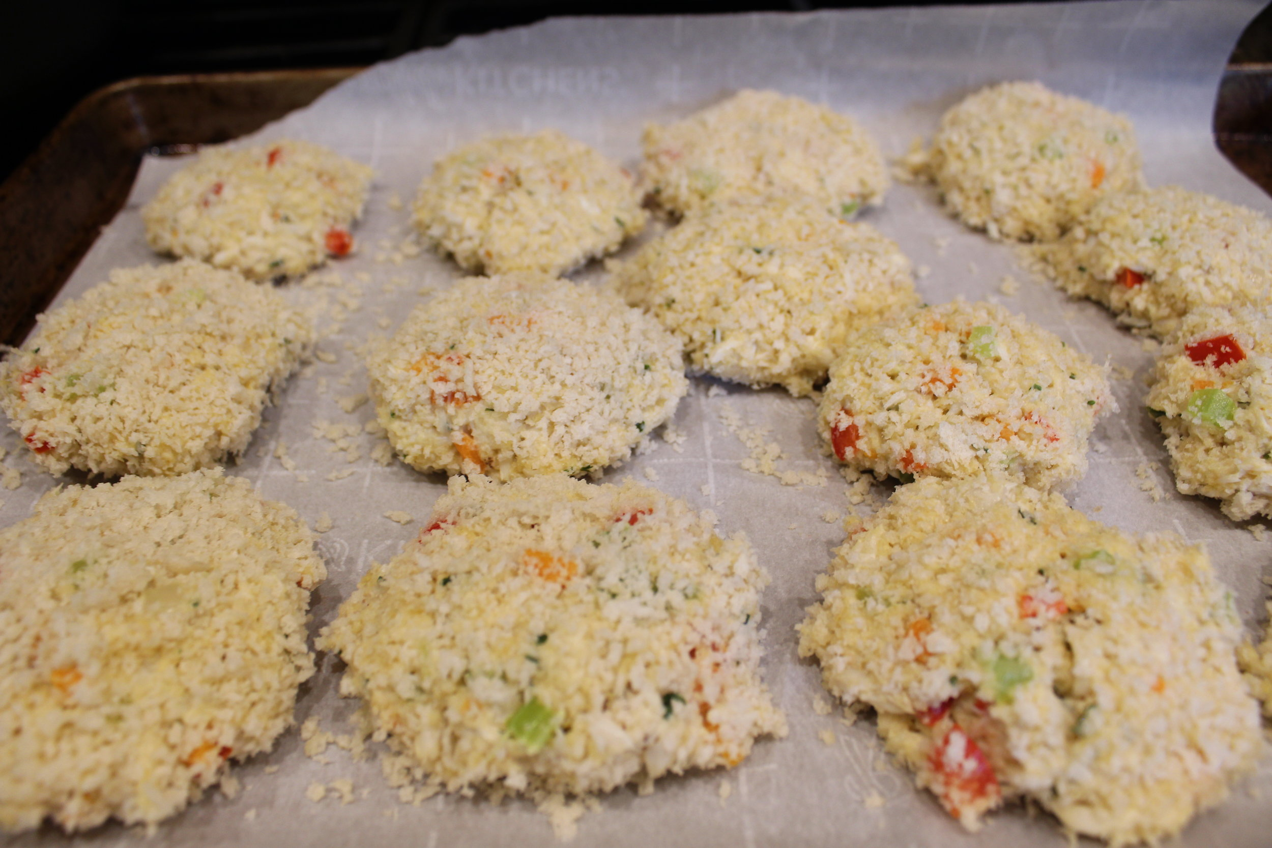 Crab cake patties ready to be browned and then baked.