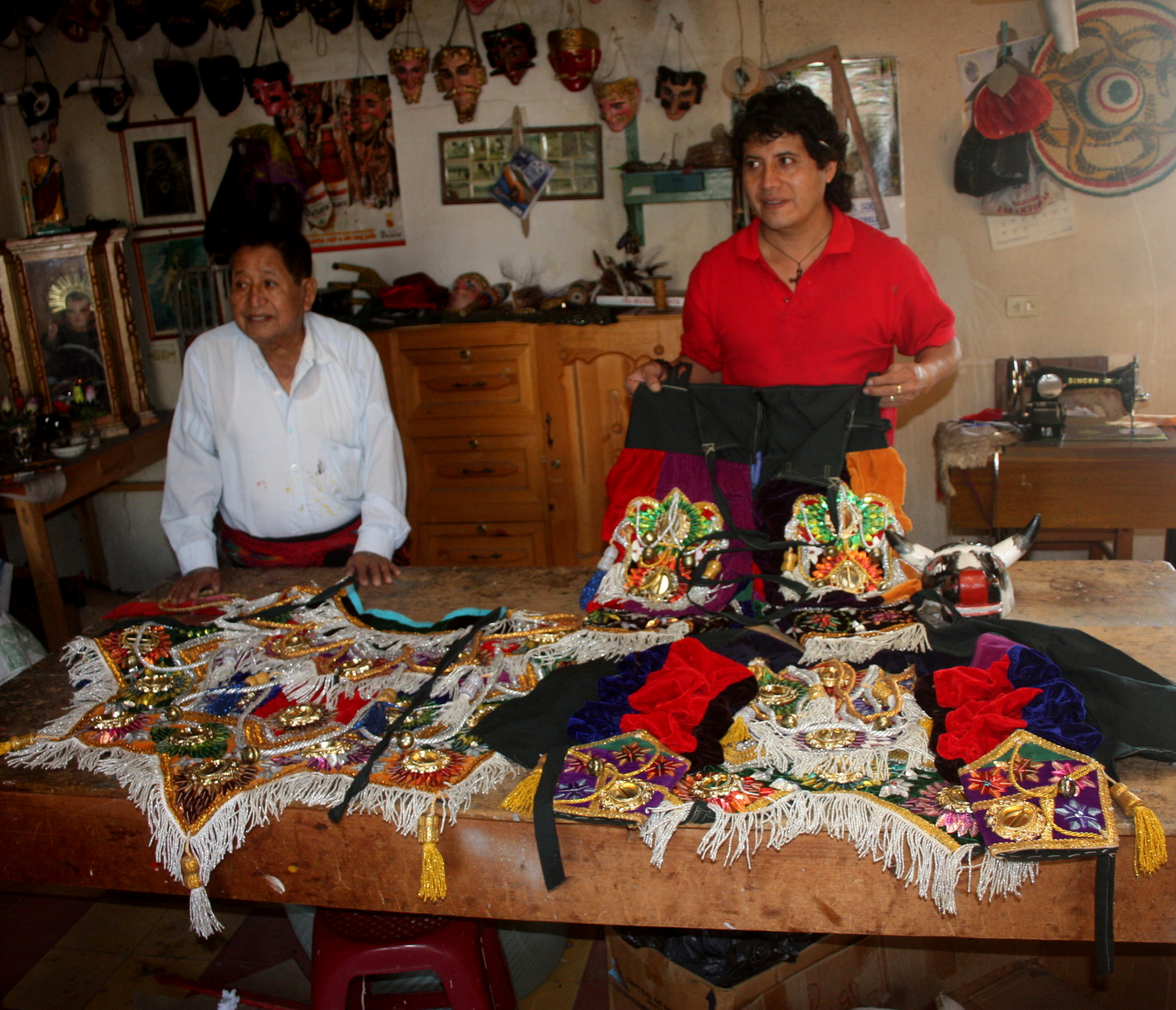 Morería  Santo Tomás, Chichicastenango 2011. Owner Don Ignacio Calel on the left and current owner-manager Angel Ignacio Ventura on the right. They are displaying a  Baile de los Toritos  costume. Note rental masks and Mexican  sombrero  hanging in the background.
