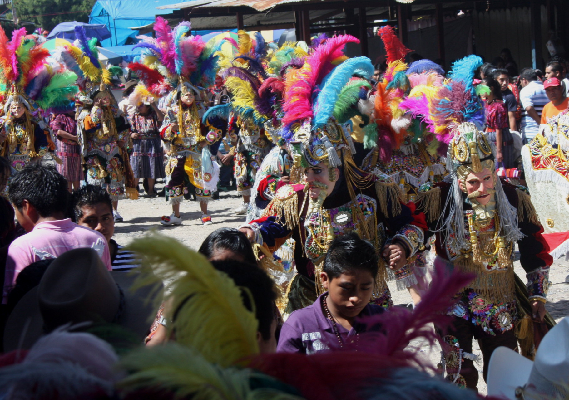 A scene from  El Baile de la Conquista de Guatemala  being danced by K'iche' performers. The pale-skinned, blue-eyed, blonde-bearded masks in the foreground represent Pedro de Alvarado and one of his captains.