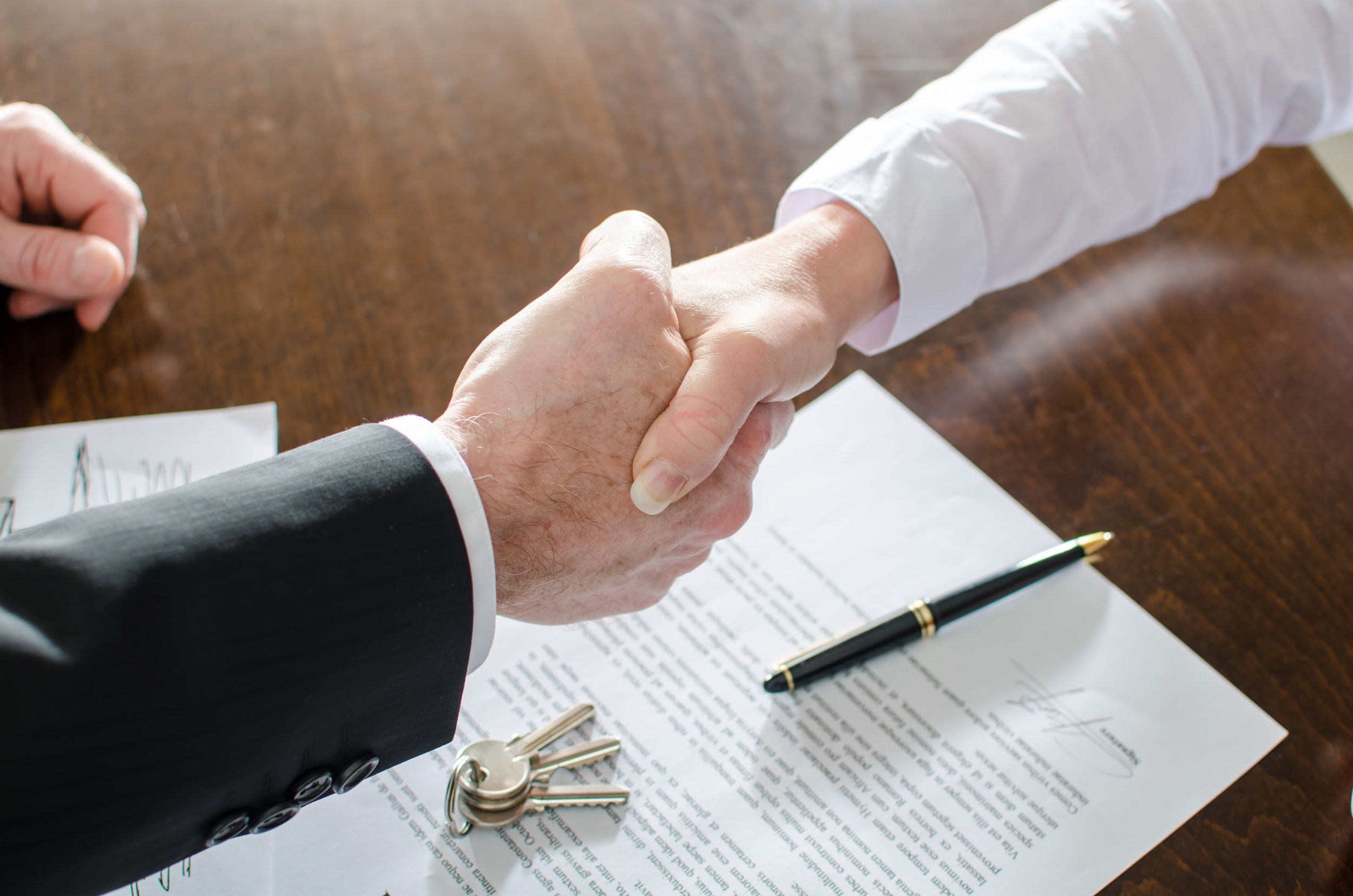 Real estate lawyer and client shaking hands over a signed document represents real estate law services.