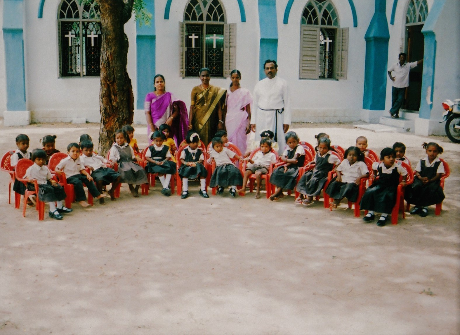 The Chennai Colony Preschool children are sitting in the chairs in India.
