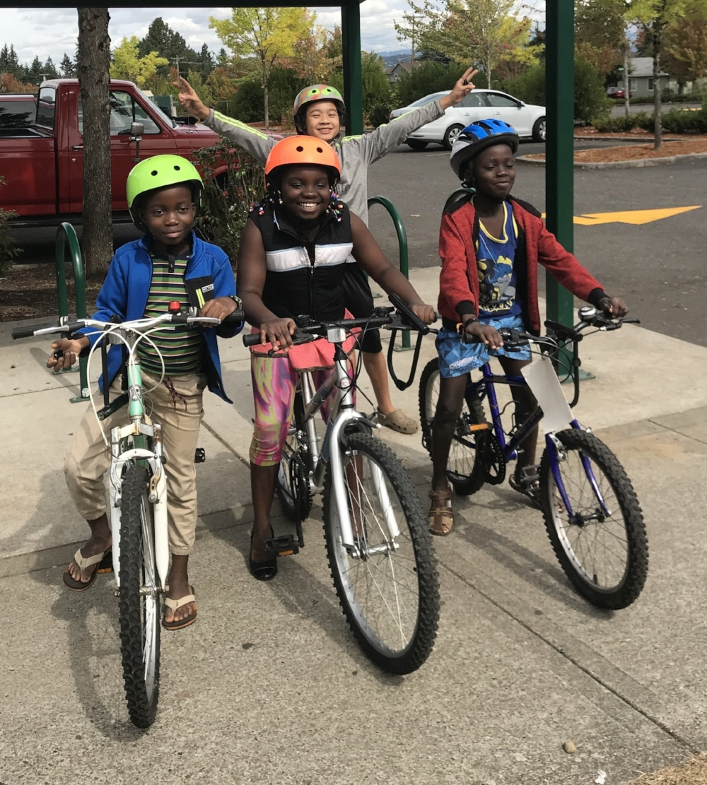 3 siblings on their new bikes, and a classmate cheerfully photobombing