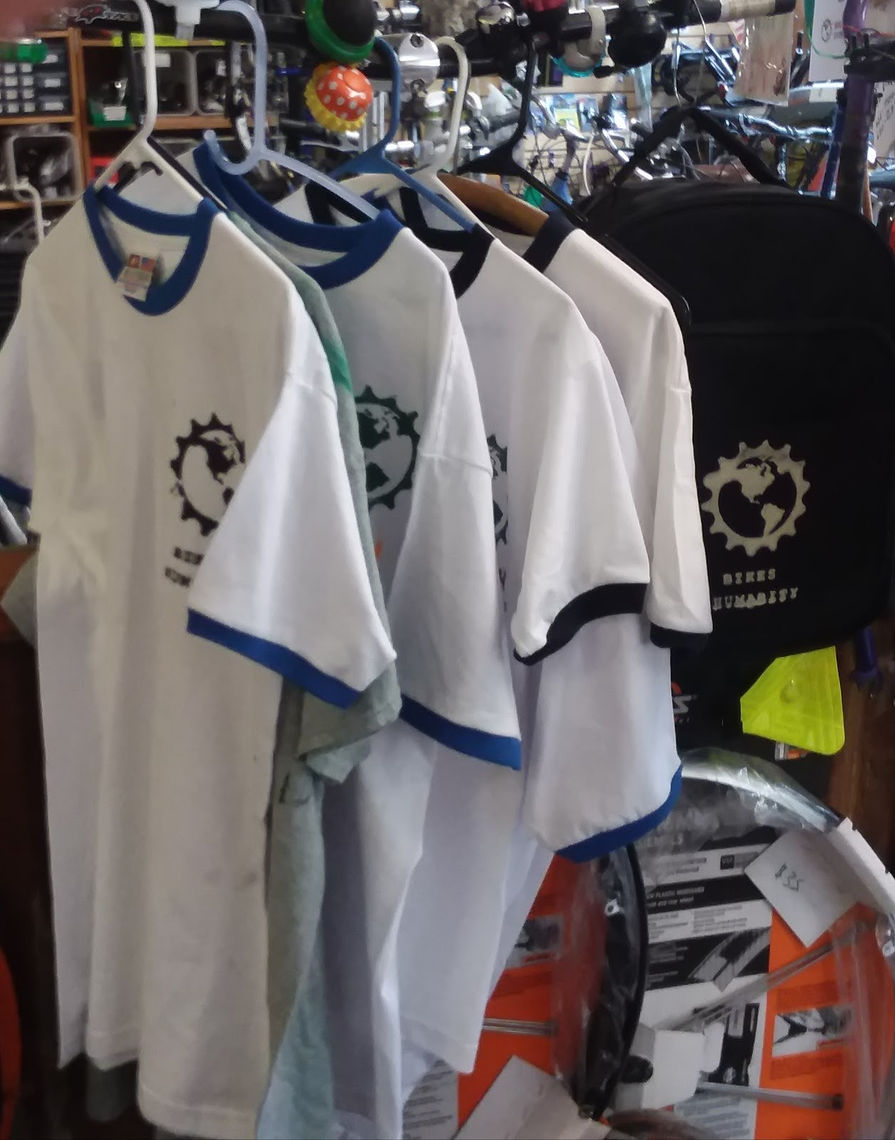 - Image Description: A row of t-shirts with the B4HPDX Earth-inside-gear logo printed on them. The shirts are hanging off of bike handle-bars.