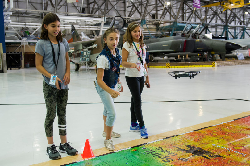 STEM Lab School students Mia Harman, 11, from left, Jennah Saleh, 11, and Avabelle Cobb,11, help direct a DJI Tello drone to land during an open house to launch a first-ever Drone Project Friday, Sept. 7, 2018 at Wings Over the Rockies Air & Space Museum.