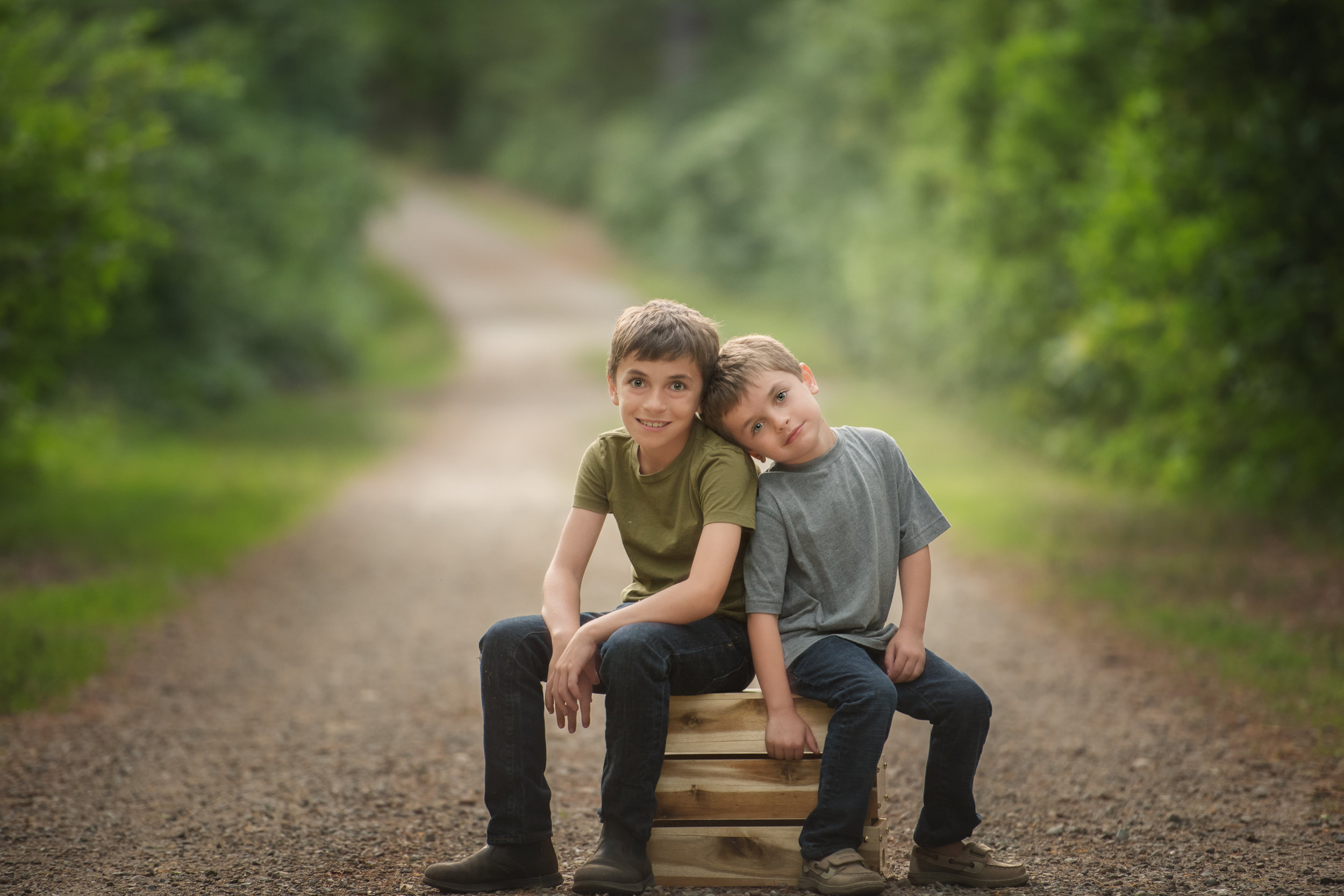 Two Boys on a Crate on a Dirt Road