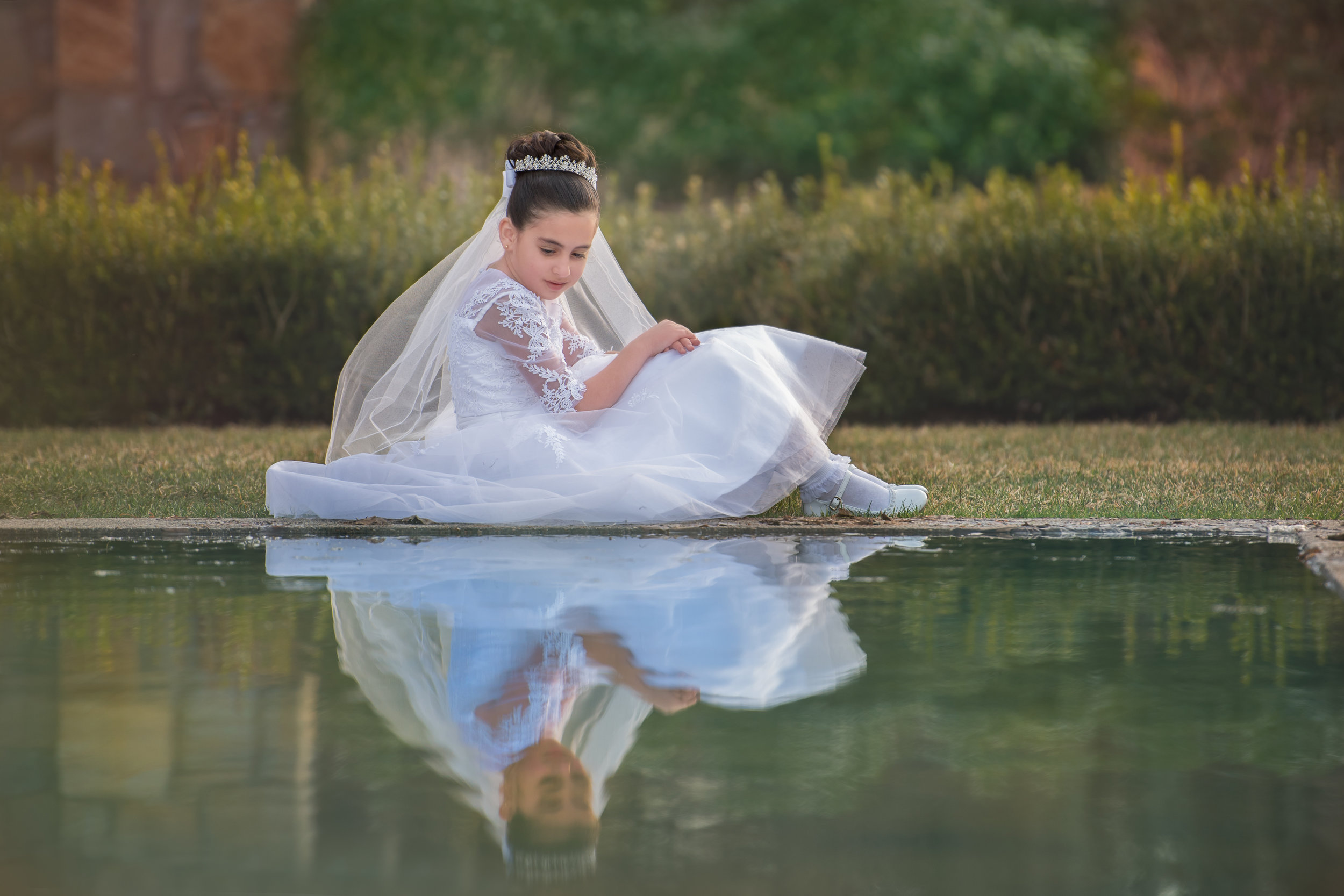 Girl in First Communion Dress by Reflecting Pool