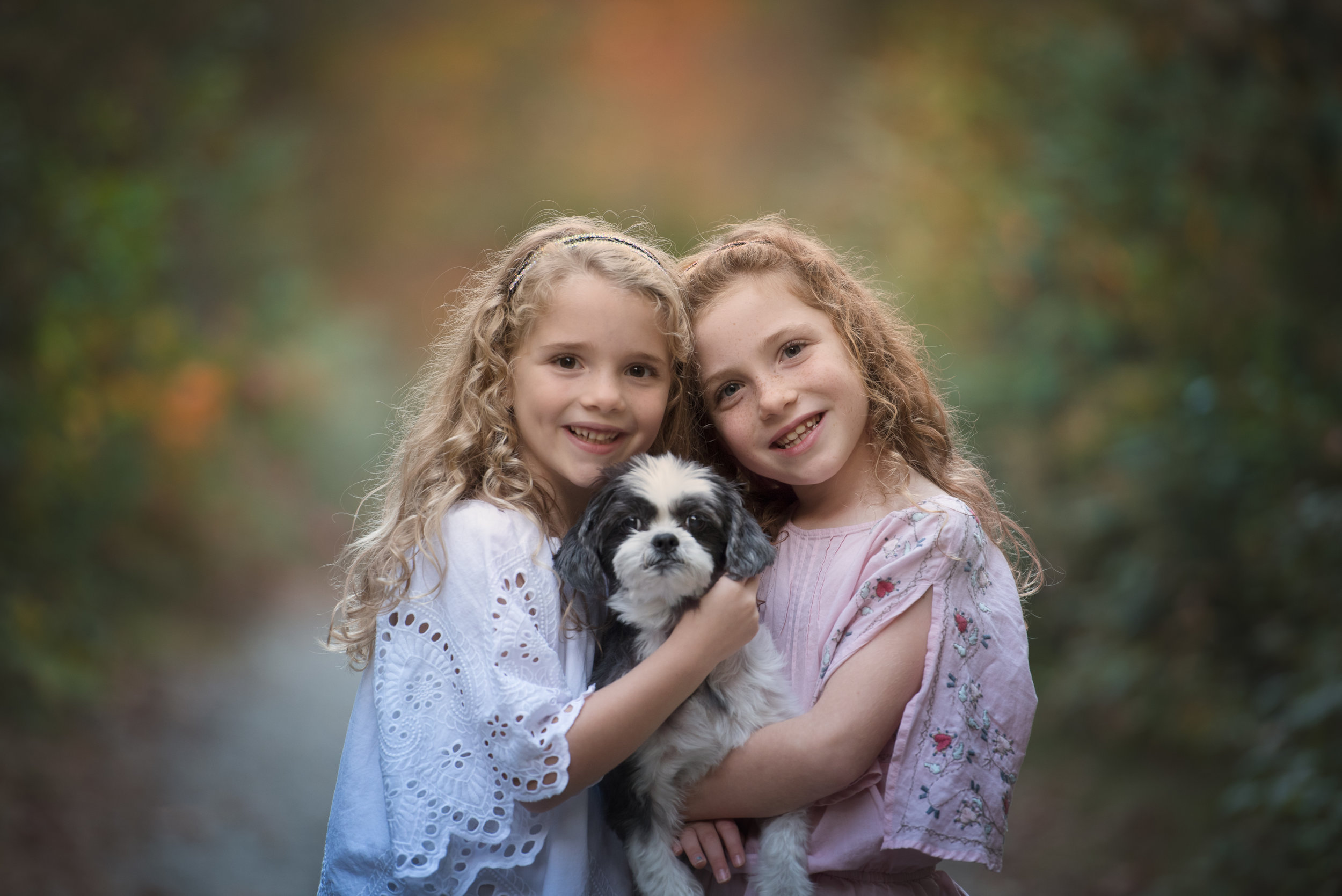 Tow Beautiful Girls Holding Their Dog