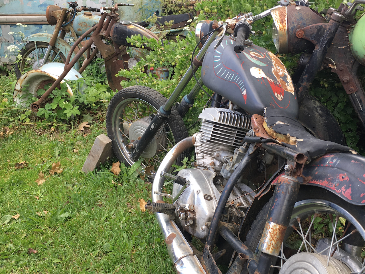 """Old motorcycles are slowly consumed by nature in a """"car graveyard"""" outside Tallinn, Estonia"""