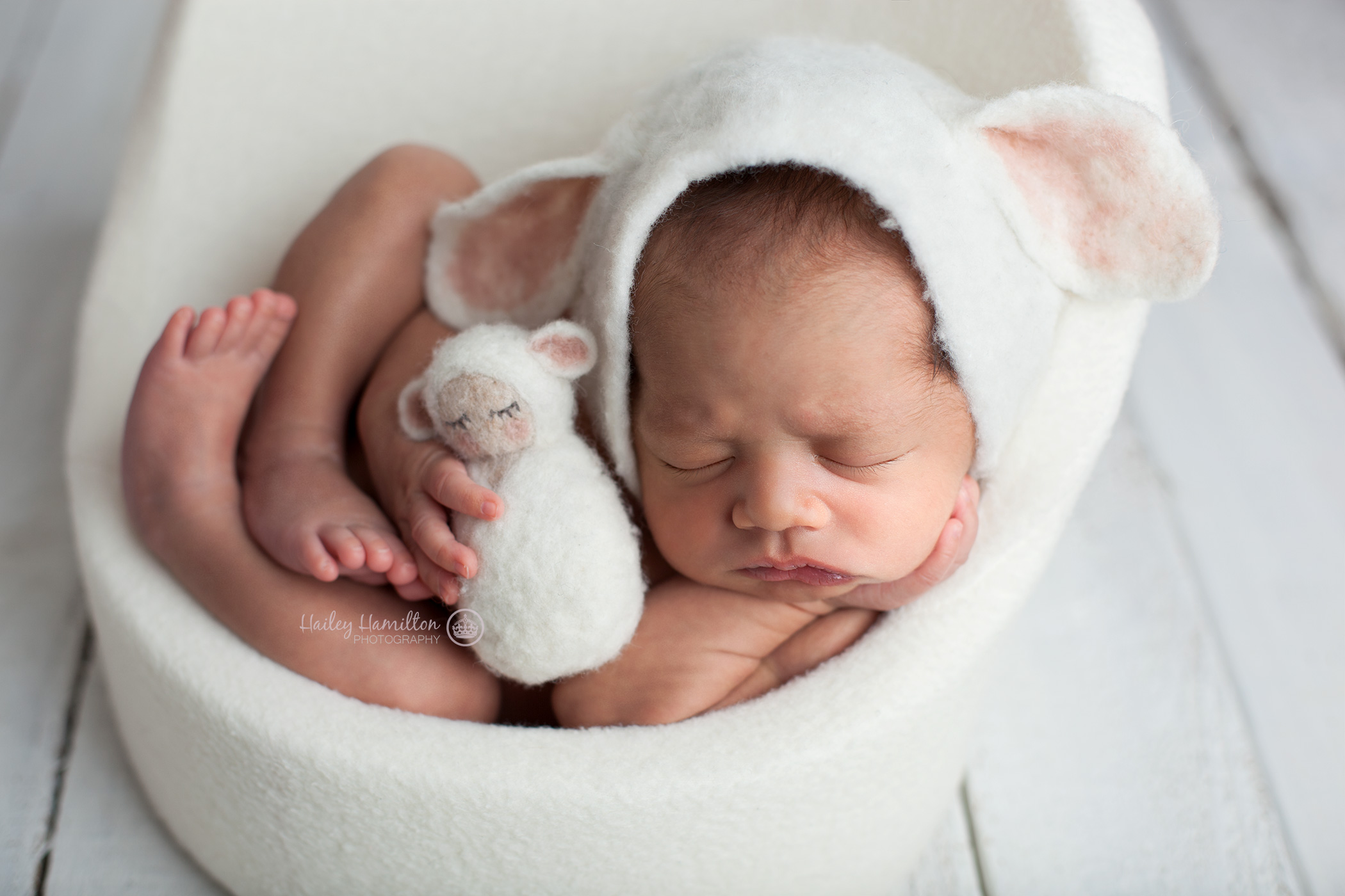 Newborn on chair prop wearing lamb bonnet