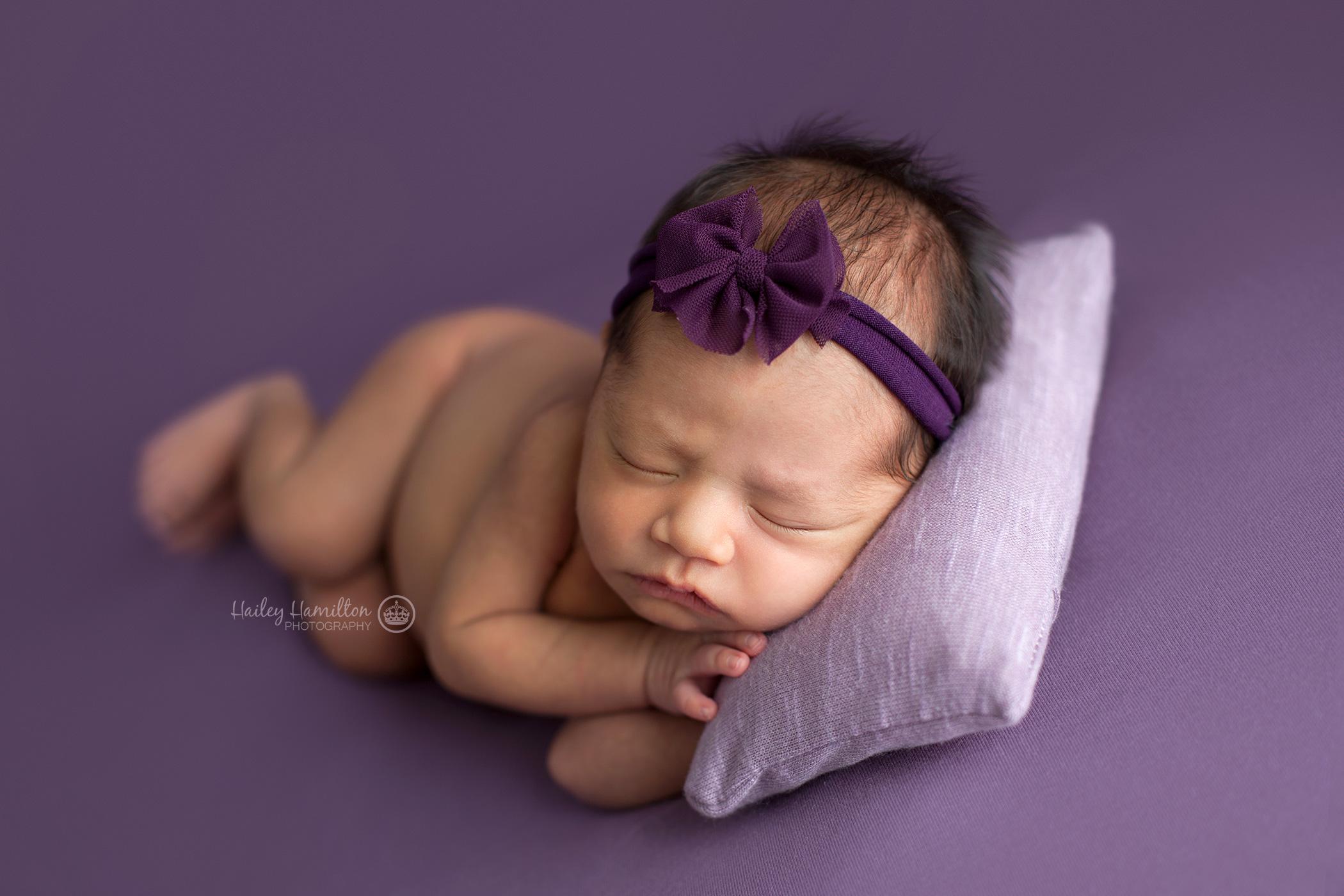 Sleepy newborn girl with purple pillow