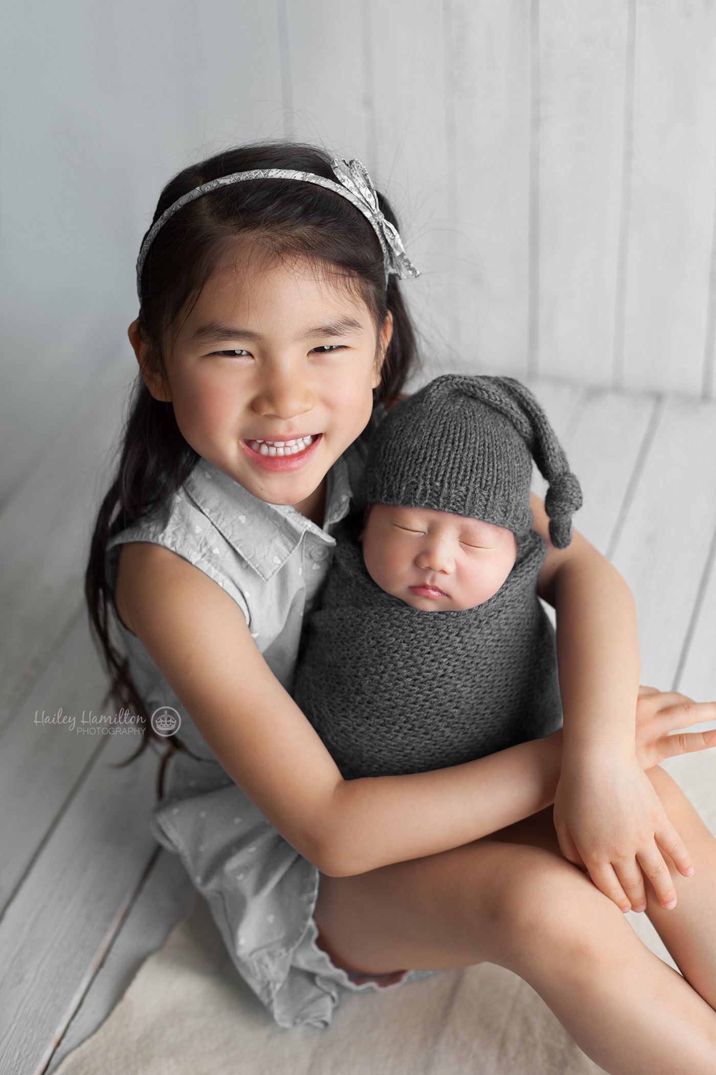 Big sister with newborn baby brother