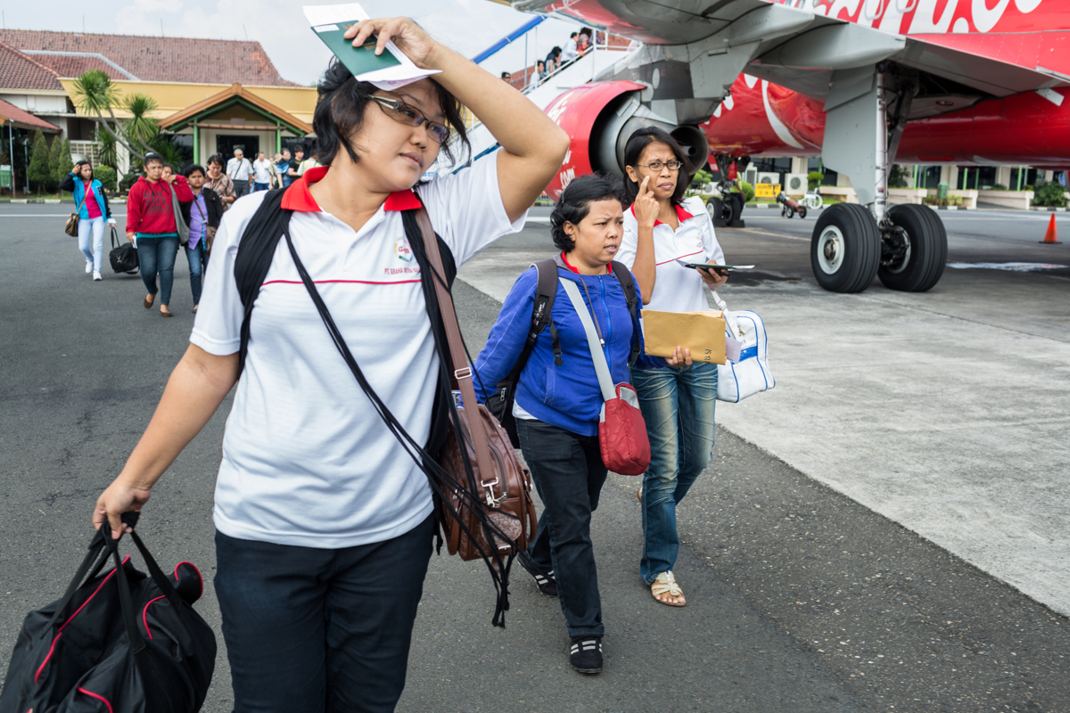 May 07, 2014 - Semarang, Indonesia. Istiana along with other migrant workers prepare to board a plane to Singapore. The women will not be able to return home for the next two years. © Nicolas Axelrod / Ruom