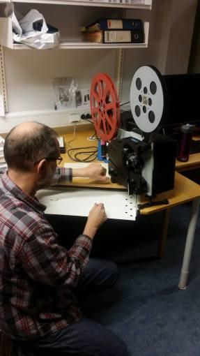 Musikkarkivar Ivar Mogstad tørker støv av 16mm filmframviseren av merket Elmo