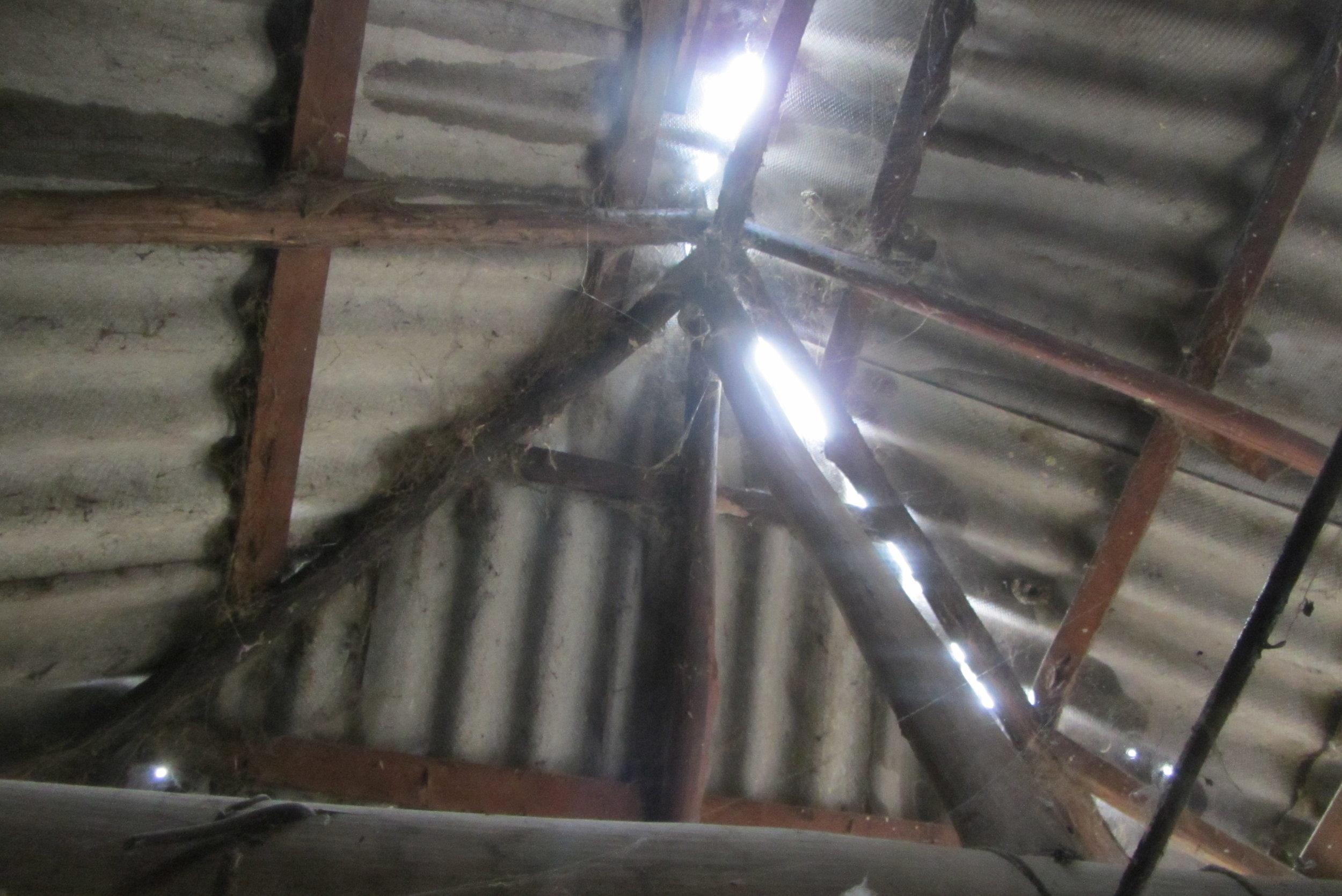 ein undichtes Asbestdach mit morschen Balken.