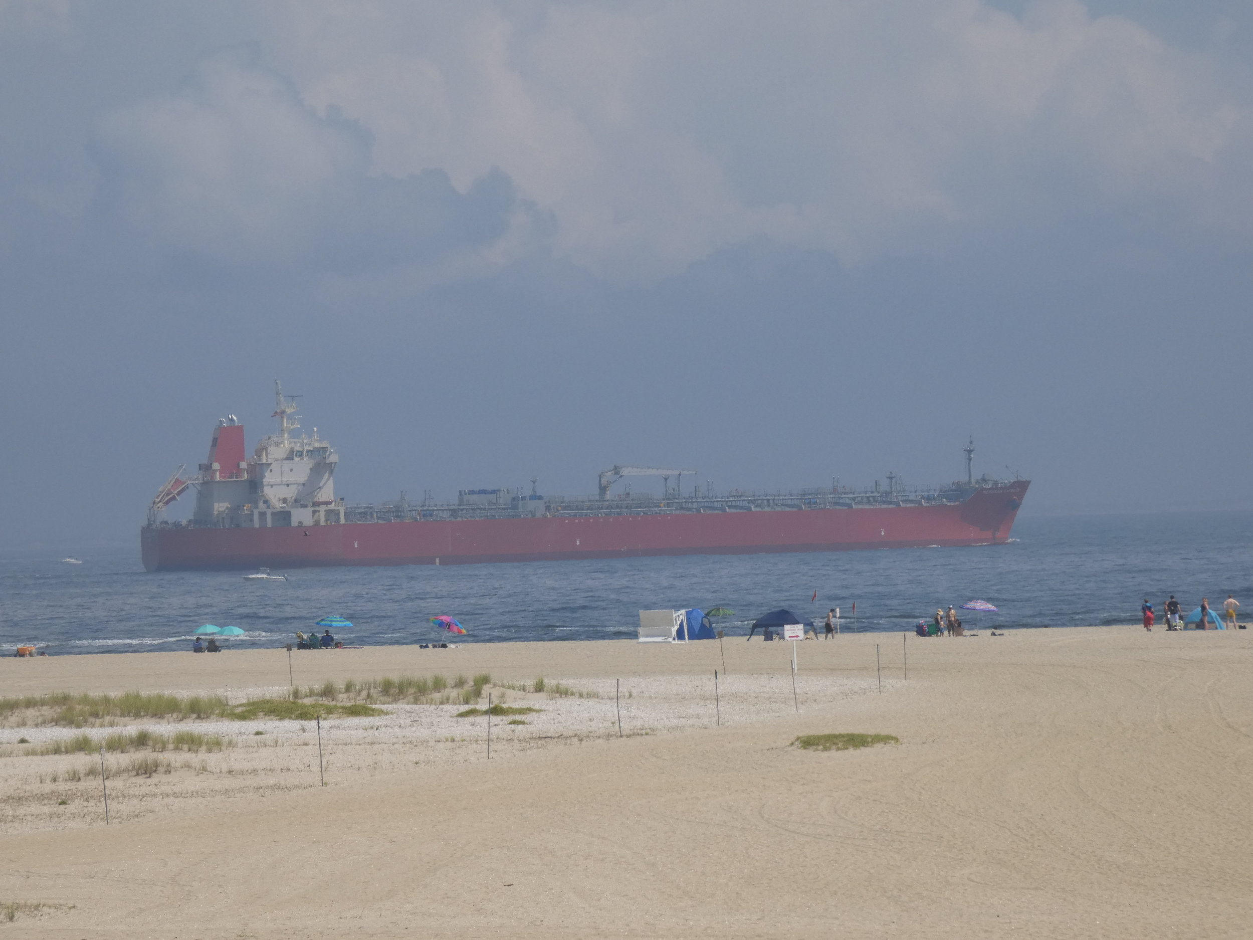Commercial cargo ships and tankers can move very close to the coast where whales sometimes feed. This picture was taken at Sandy Hook, Gateway National Recreation Area, North Beach, at the entrance to New York Harbor during August 2019.