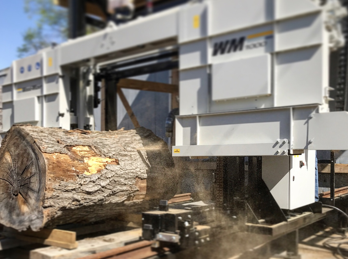 The mill is designed to program the size of each slab on the machine's control pad. A large bandsaw runs the circumference of the machine's chassis and precsily saws the log into live edge slabs.