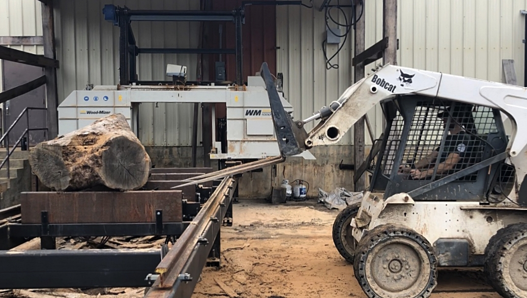 Once the log arrived at Eutree's sawmill, it is loaded onto the Wood-Mizer 1000 with the Bobcat.
