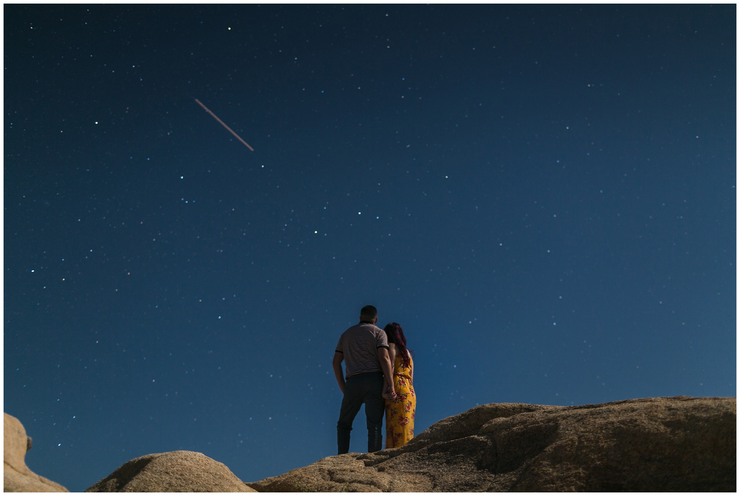 couple standing under the stars on rocks in Joshua Tree
