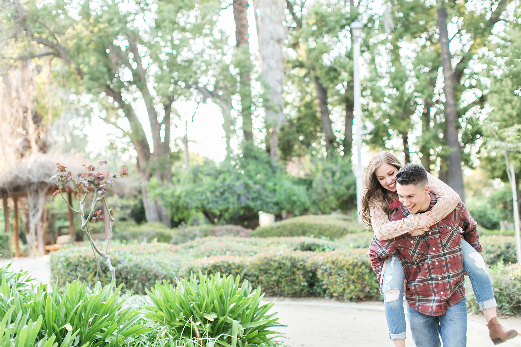 Engaged couple giving piggy back ride during engagement session at Sylvan Park in Redlands, Carrie Vines Photography
