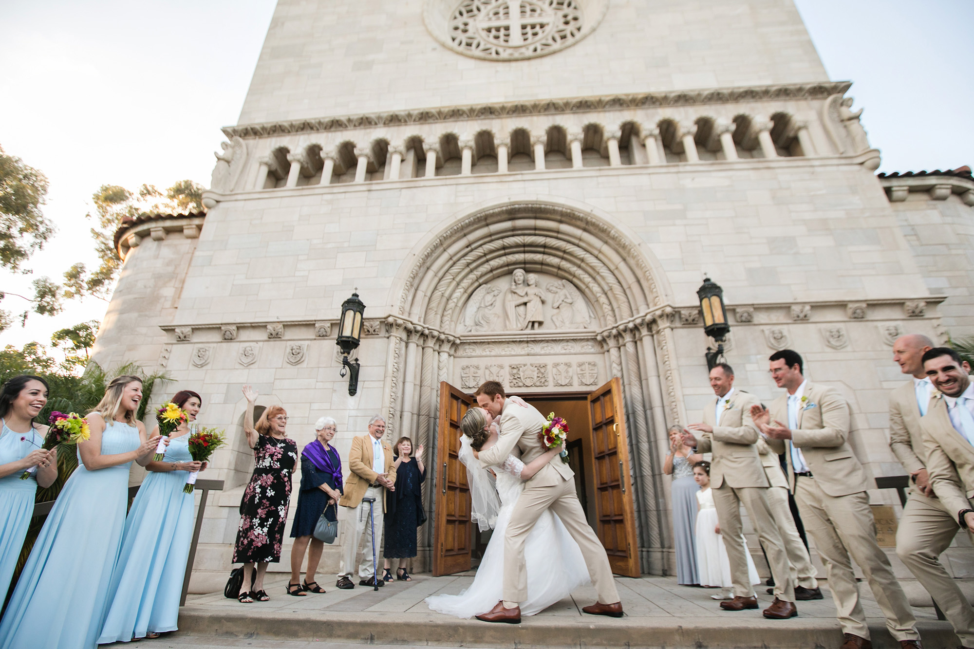 Amy and Rob's St. Monica Catholic Church Wedding bride and groom kiss in front of the chapel Carrie Vines Photography