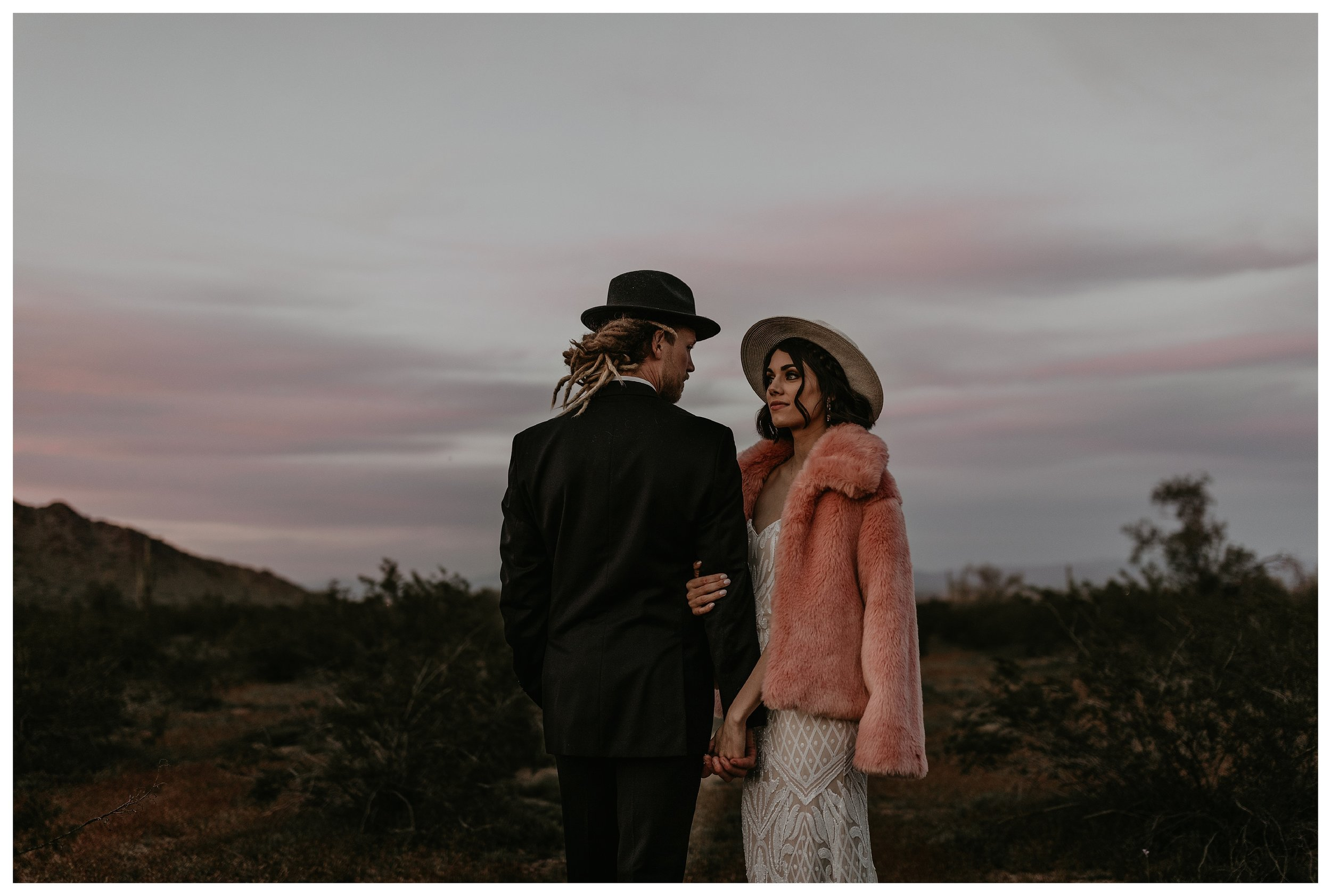 sunset bride and groom portraits in the desert with a large pink faux fur jacket
