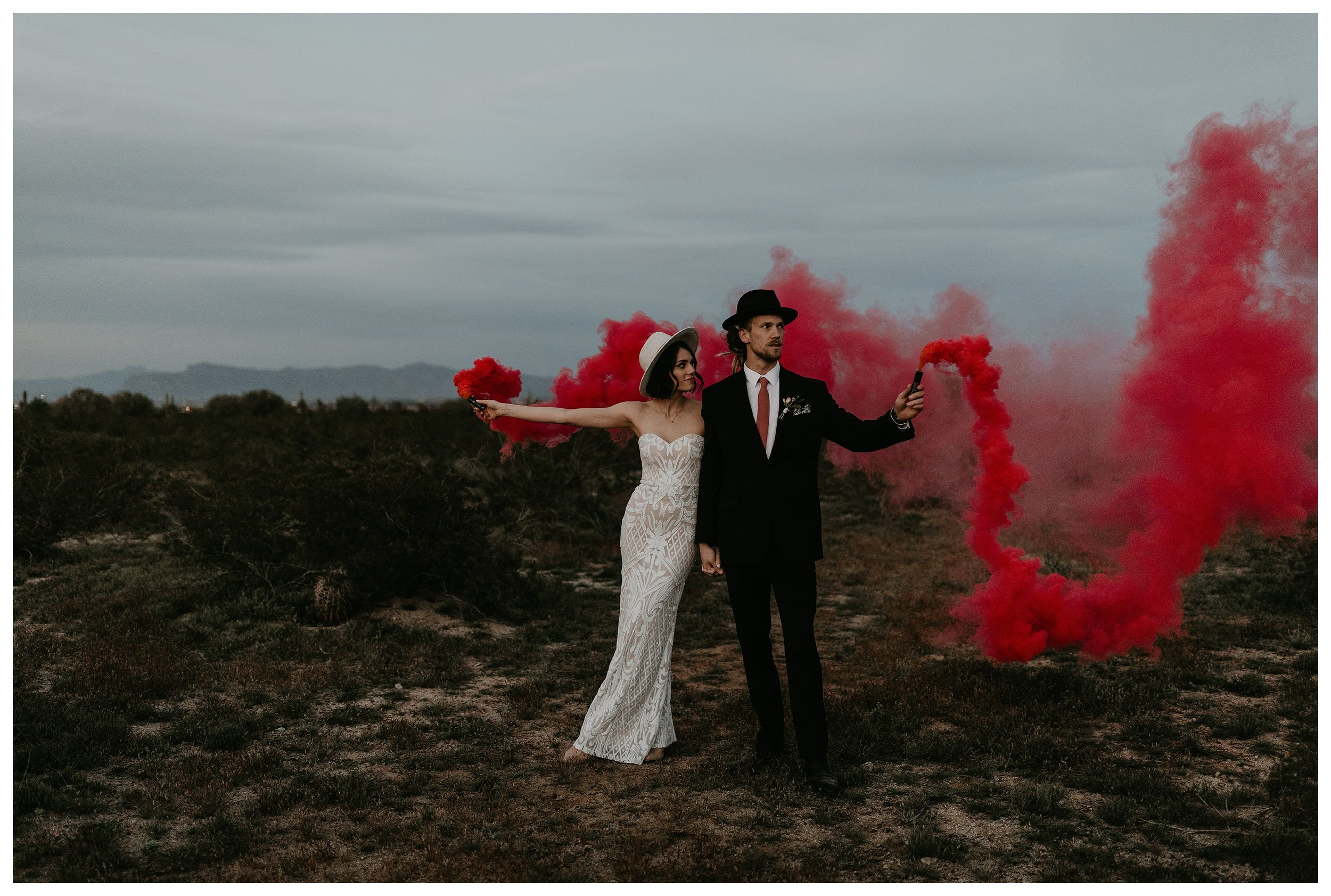 bride and groom red smoke bomb portraits in the desert at sunset