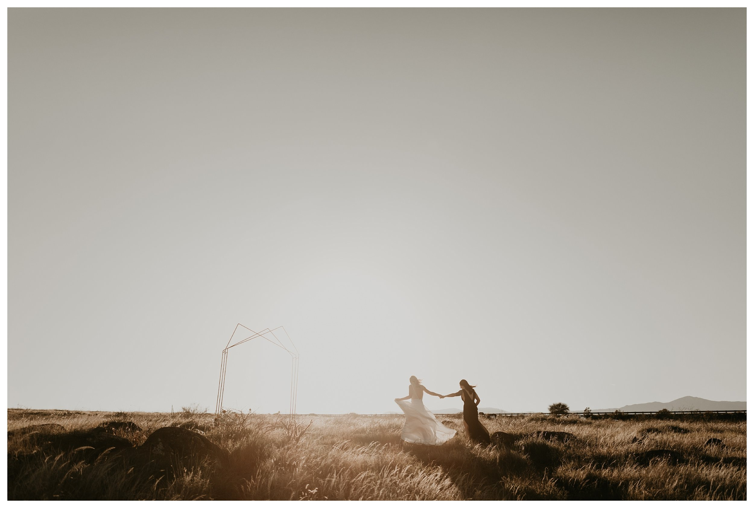 two brides walking up to their geometric alter at golden hour in a large field