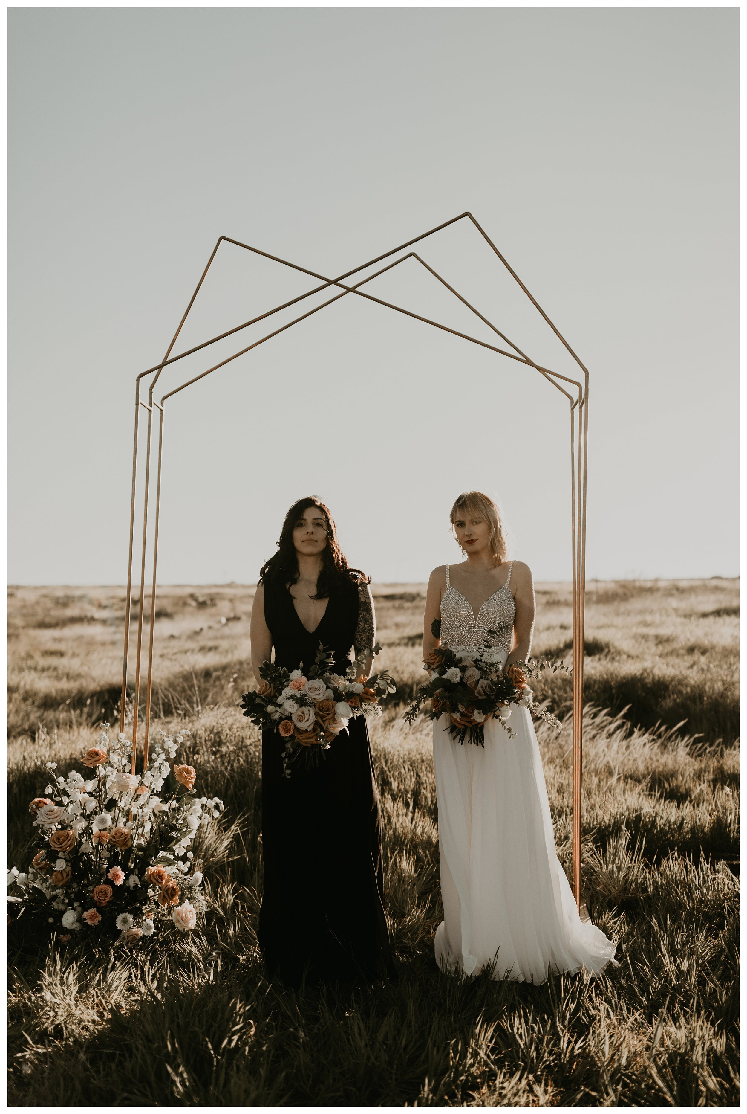 same sex elopement with two brides and a geometric arch in an open field