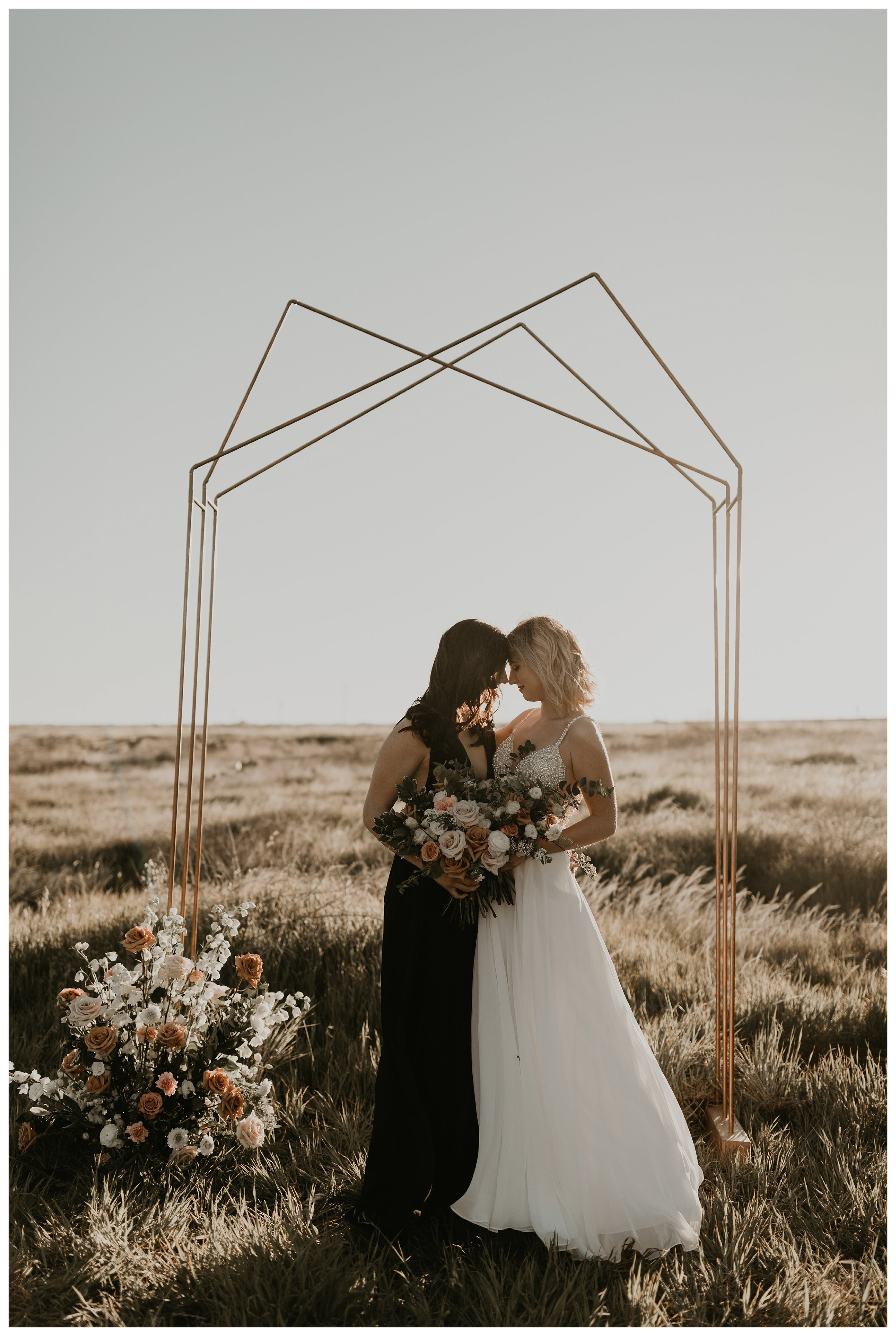 Same sex elopement with geometric arch during golden hour