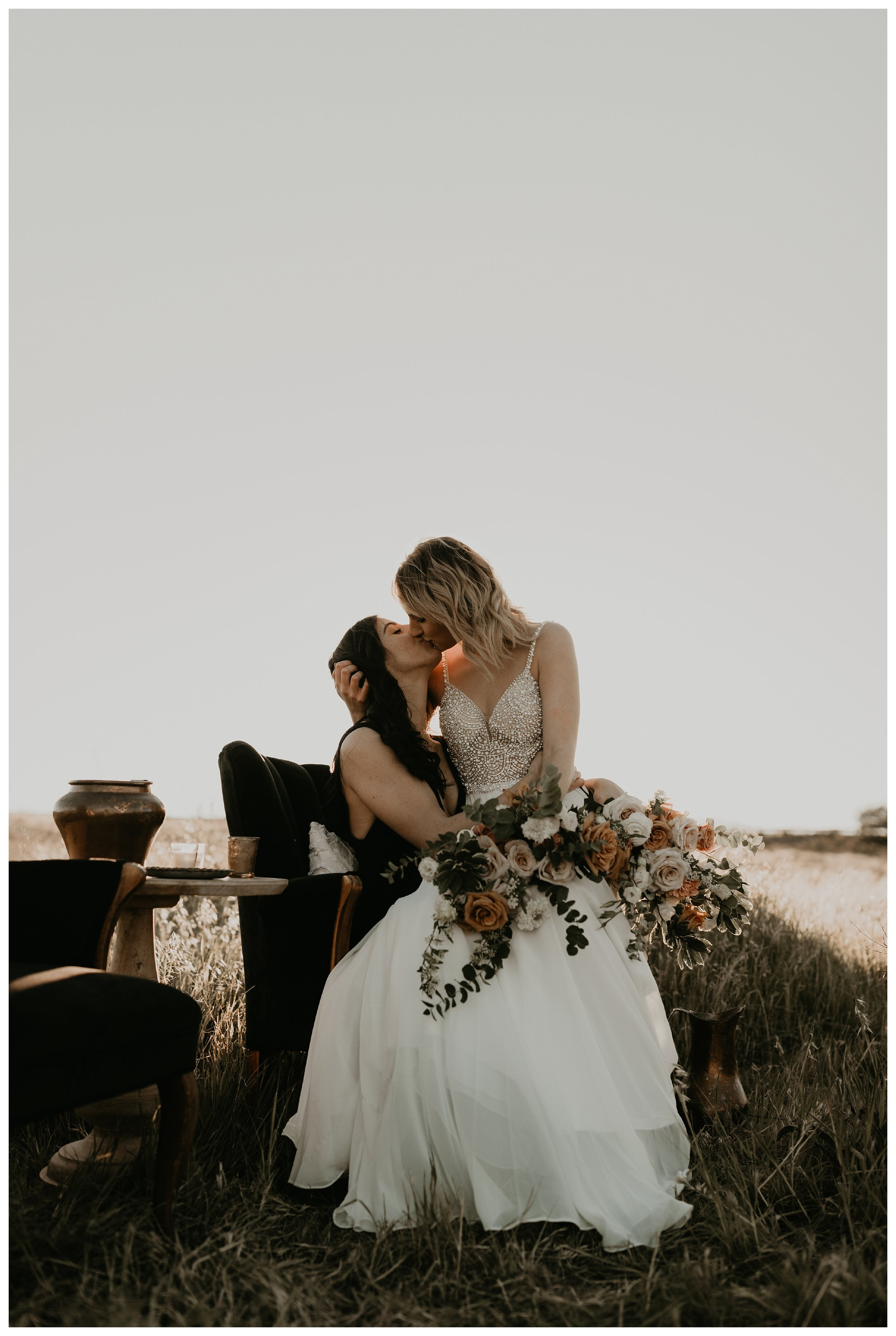Same sex elopement during golden hour with black and white dresses and blush florals and vintage seating area