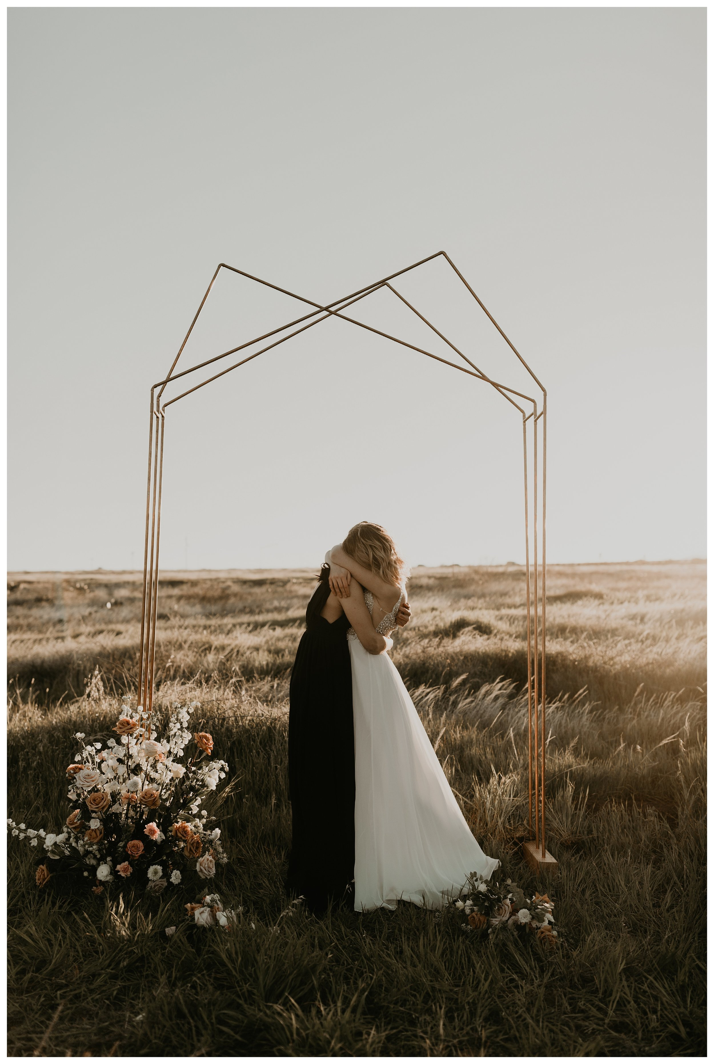 same sex elopement reading their wedding vows with geometric arch