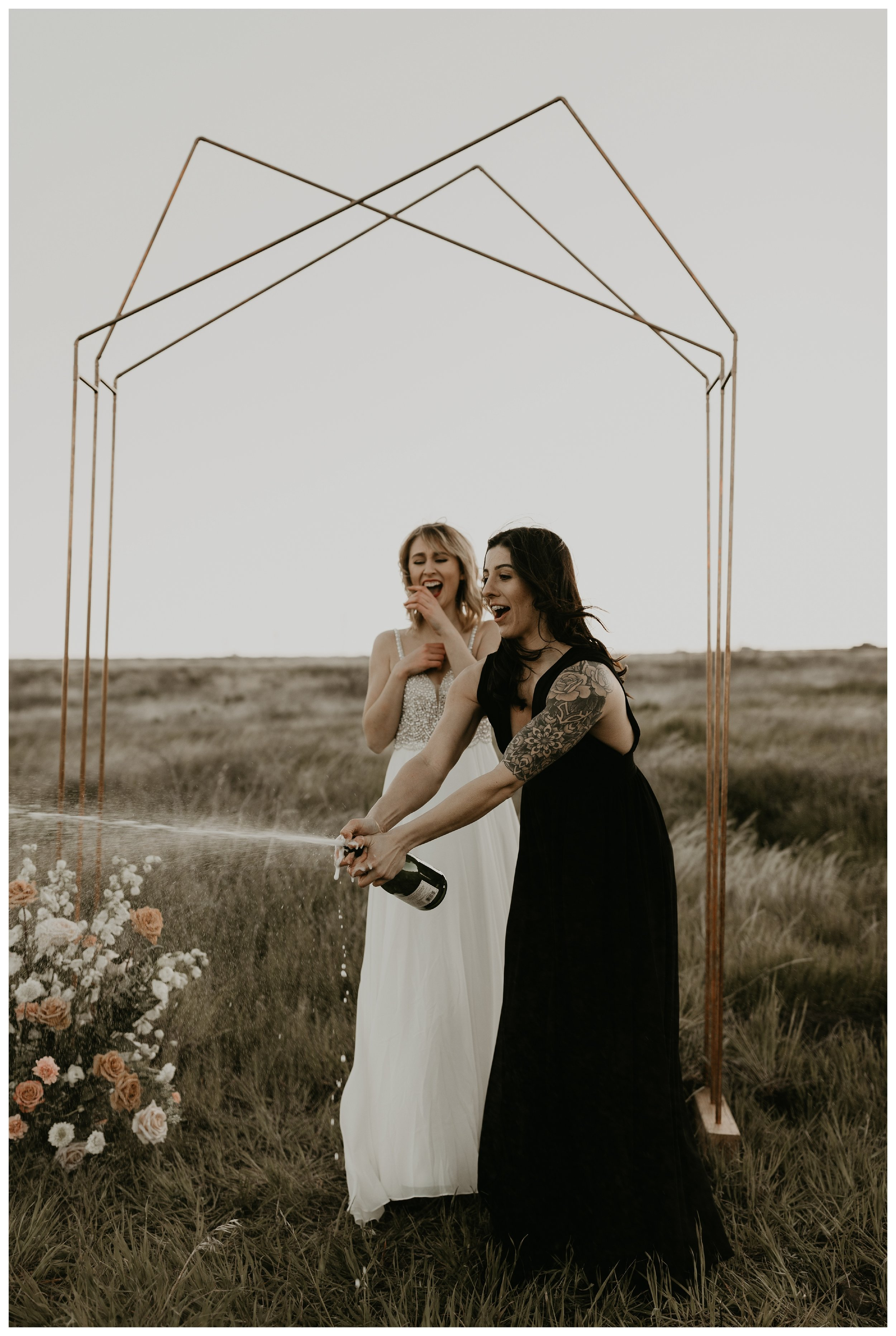 same sex elopement popping champagne with geometric rose gold arch