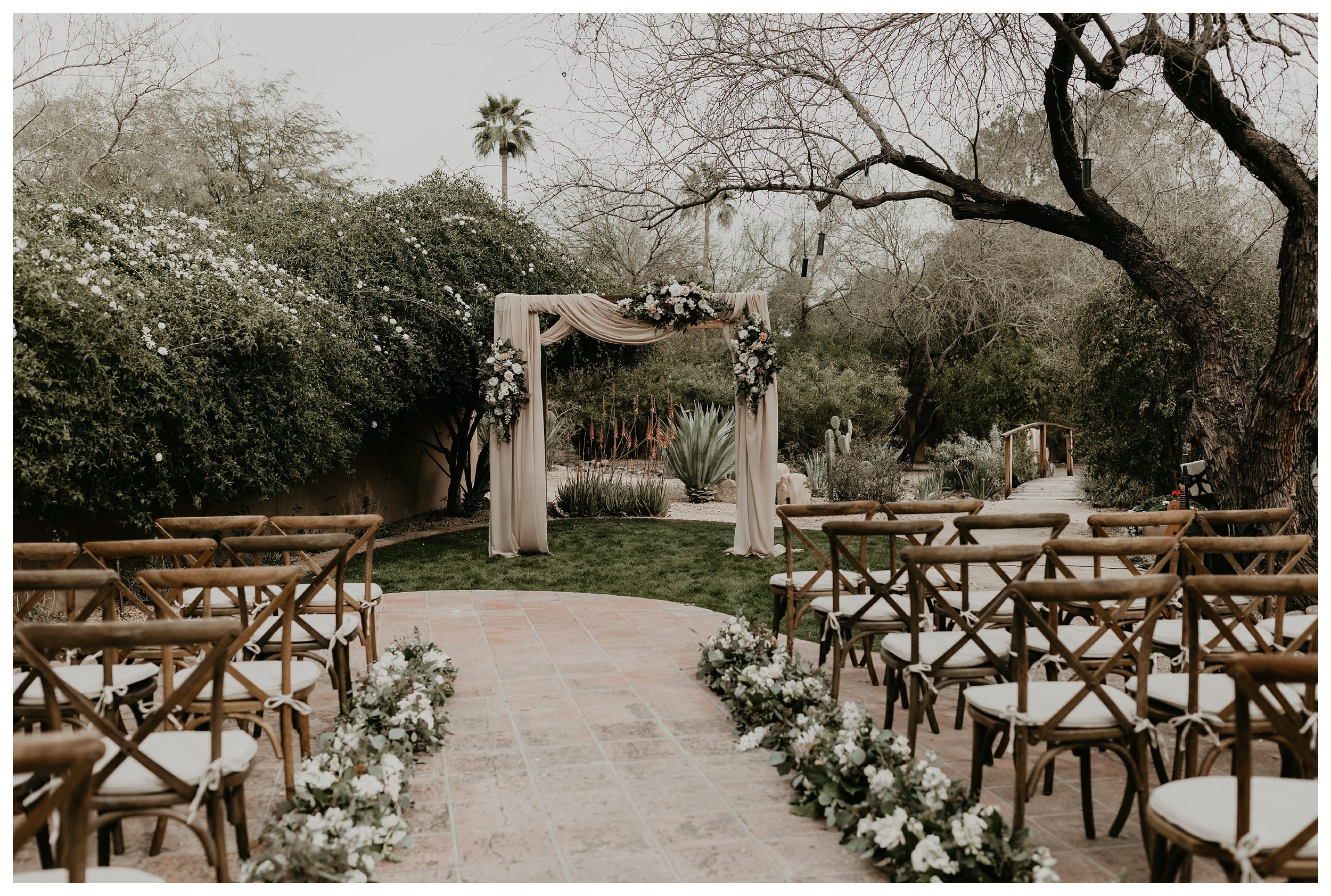 Ceremony area at Hermosa Inn in Arizona with cloth-wrapped alter wood wedding seating and greenery wedding decor and florals