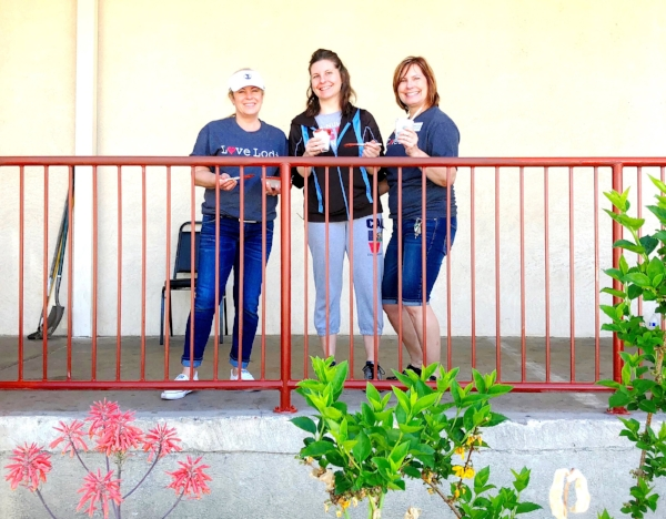 """""""We're out here to give back to our community. We put a team together to give back to the community we love, and it's great to see everyone here from all different walks of life working together."""" REMAX office sanding and repainting the railing in front of Salvation Army, along with a few of their clients, lenders and churches."""