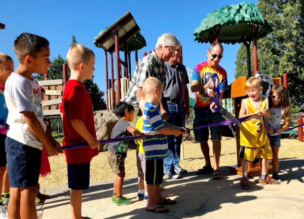 Lodi City Councilmen Mark Chandler, Parks Director Jeff Hood, Parks Committee member Bill Mitchell and neighborhood kids cut the ribbon welcoming Henry Glaves' new park playground.
