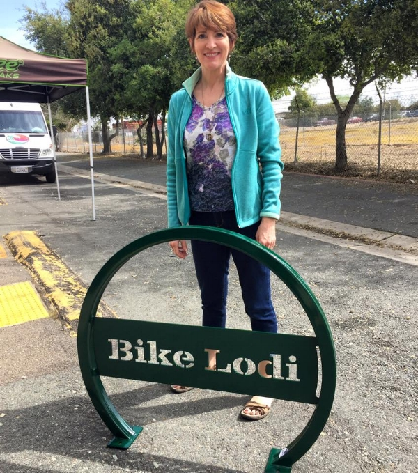 Bike Lodi's Kathryn Siddle poses with one of the bicycle racks purchased and installed in downtown Lodi through Bike Lodi. Picture from  Bike Lodi's Facebook .
