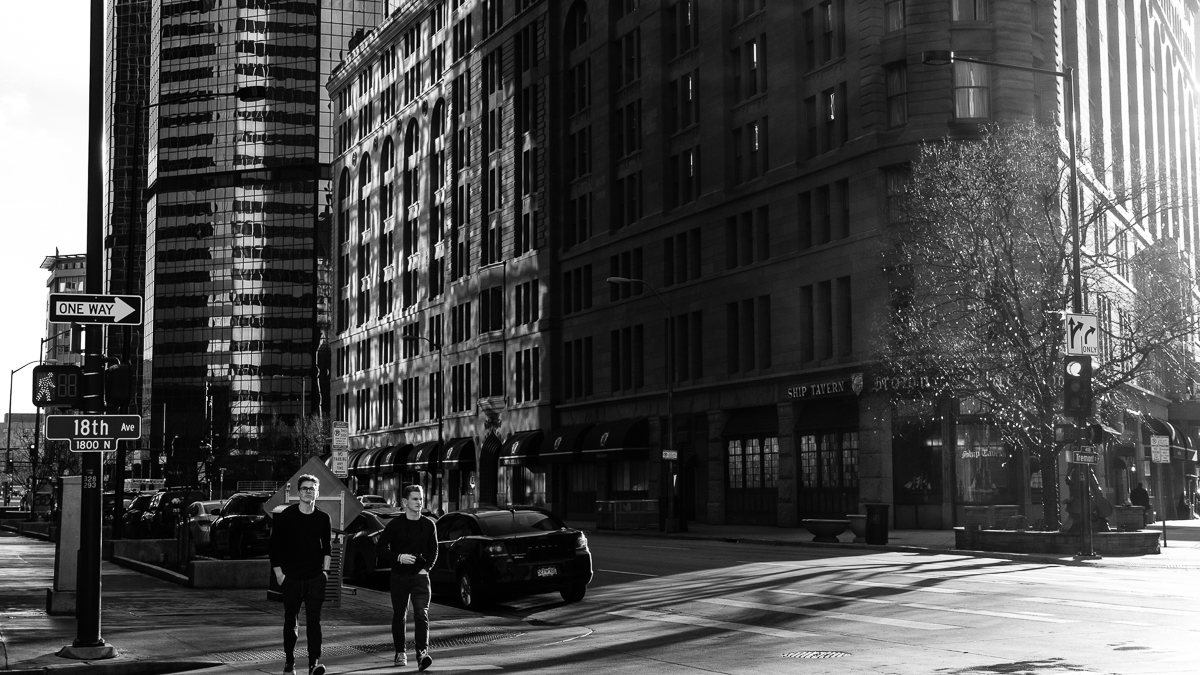 Late afternoon sun streams down Tremont Street along the Brown Palace onto Broadway and the sun reflects off of the sky scrapers back onto the Brown Palace as two pedestrians cross the street at 18th. I cropped this in a 16X9 format. - Fuji XT-2, XF 35mm f/2, Acros R Film Simulation