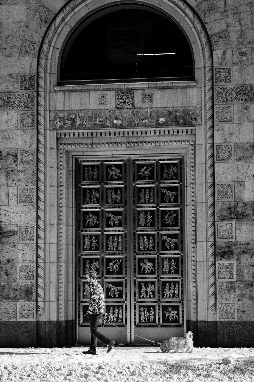 Day 57 - 365 Day B&W Photo Challenge - Man out walking his dog in front of the CoBiz Bank Building at 17th and Champa in Denver, Colorado. - Fuji XT-3, XF 56mm f/1.2, Acros R Fim Simulation