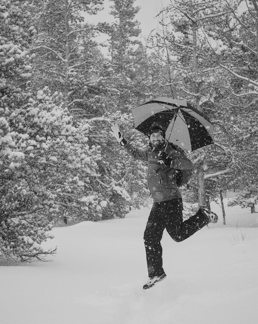 Day 64- 365 Day B&W Photo Challenge - Ventured out in the snow yesterday up to Rocky Mountain National Park with some friends during the light morning snow.  This is my friend Chase jumping up in the air with his umbrella on the trail. - Fuji XT-3 XF 35mm f/2, Acros R Film Simulation