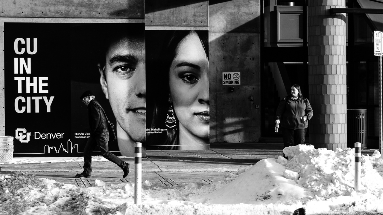 """Day 67- 365 Day B&W Photo Challenge - Walking in front of the """"CU in Denver"""" advertisement in front of the University of Colorado Denver Campus building. - Fuji XT35 XF 35mm f/2, Acros R Film Simulation"""