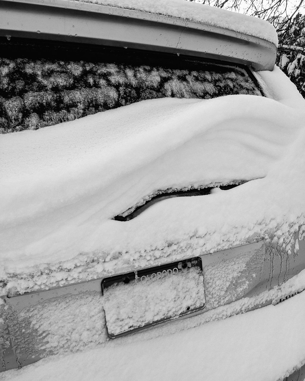 Day 104 - 365 Day B&W Photo Challenge - Their wasn't that much snow here from the Bomb Cyclone Pt2, but it start off wet, drift and freeze over last night. You can see the drifting and ice on the back of my 4Runner's back window. - Google Pixel 3, VSCO Neopan 400 preset