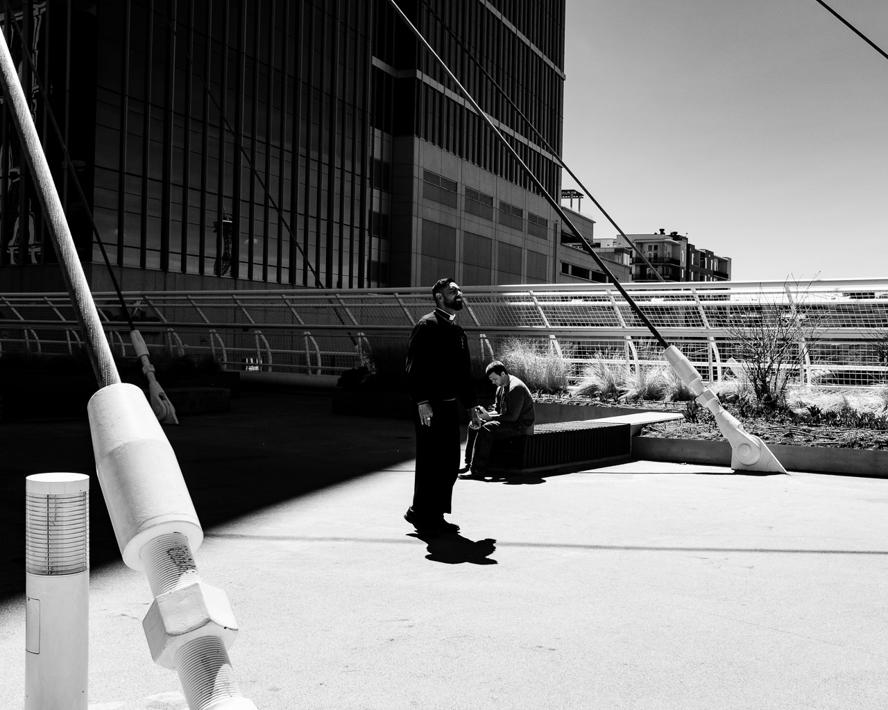 Day 110 - 365 Day B&W Photo Challenge - Priest walks into the light of the daytime sun on the Millenium Bridge in Denver, Colorado - Fuji X100F, Acros R Film Simulation