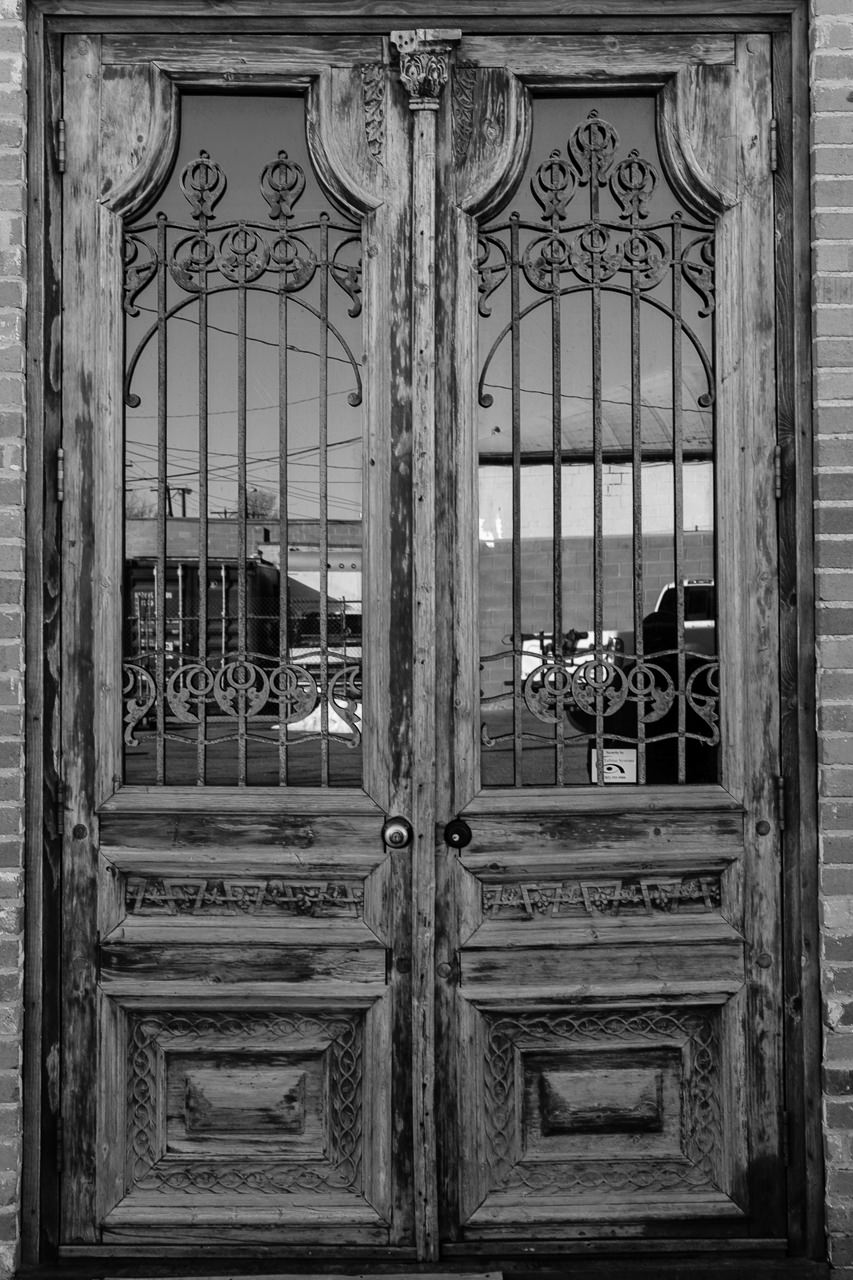 Day 116- 365 Day B&W Photo Challenge - The texture and design details of these antique entrance doors caught my eye. Fuji X-T3, XF 35mm f/2, Acros R Film Simulation