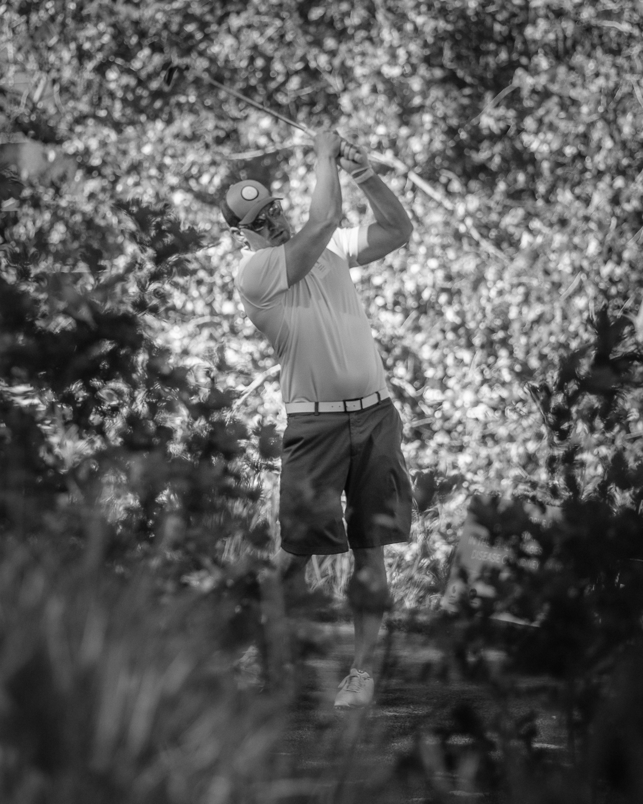 Day 177 - 365 Day B&W Photo Challenge - I was doing a little charity work for the National Kidney Foundation yesterday capturing images for the NKF Golf Classic and captured this golfer's tee shot through the bushes. -  Fujifilm X-T3, XF 50-140mm f/2.8, Acros R Film Simulation