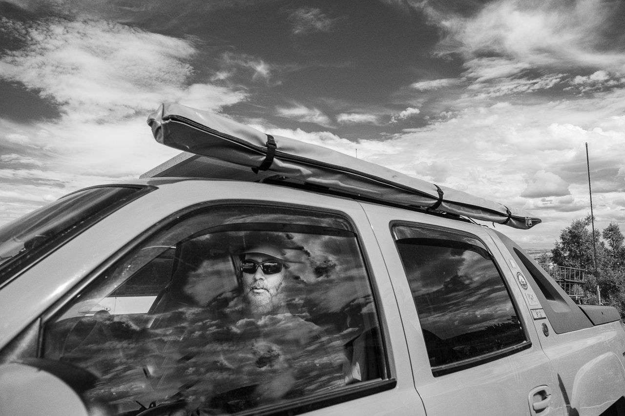 Day 217 - 365 Day B&W Photo Challenge - Neal's face pierced through the cloud reflections in the glass on his truck. - Fuji X-T3, XF 14mm f/2.8, Acros  R Film Simulation